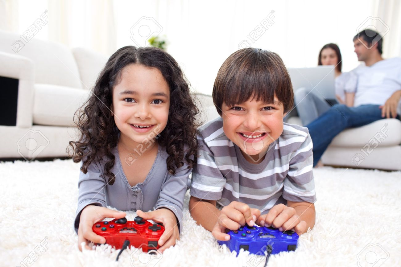 Smiling siblings playing video games lying on the floor Stock Photo - 10250341