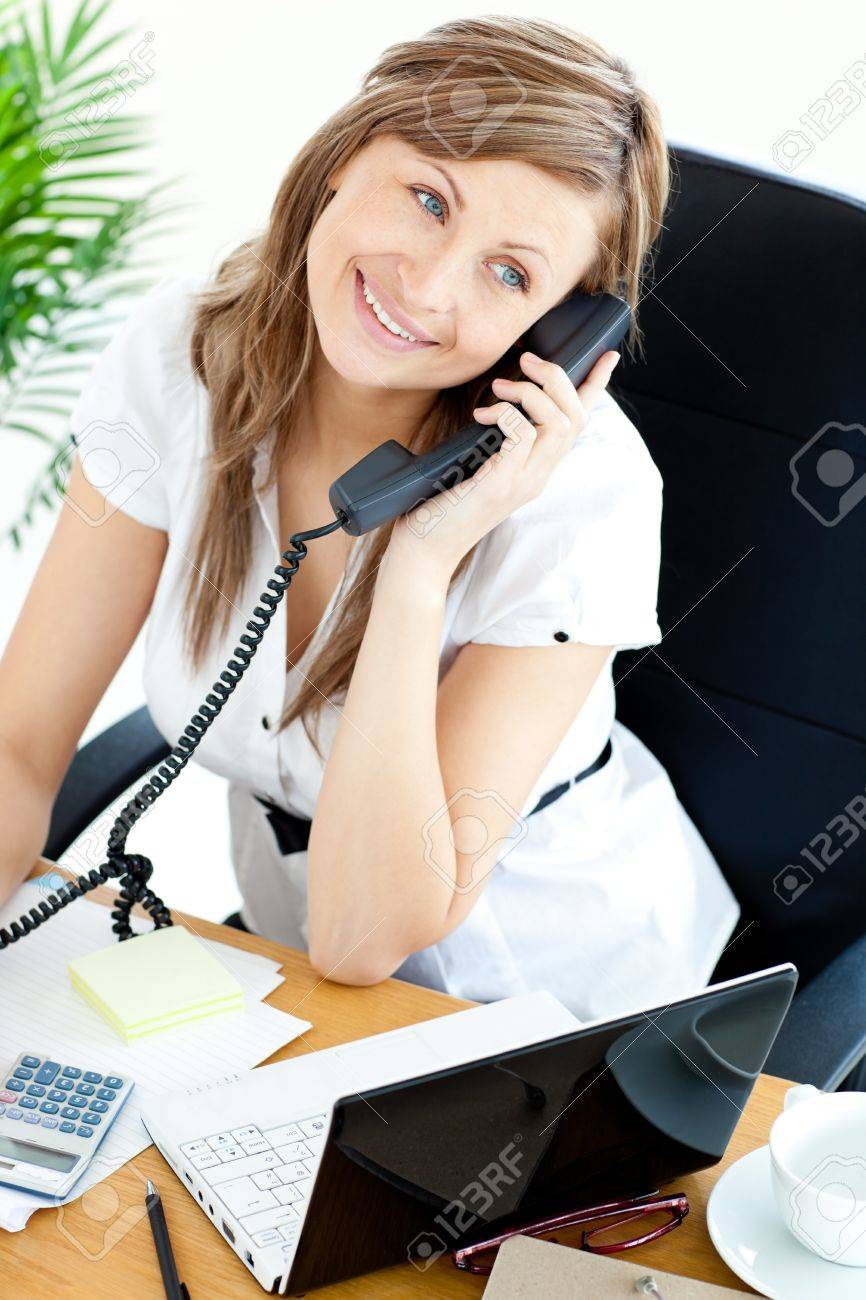 Bright businesswoman talking on phone sitting in her office Stock Photo - 10249892