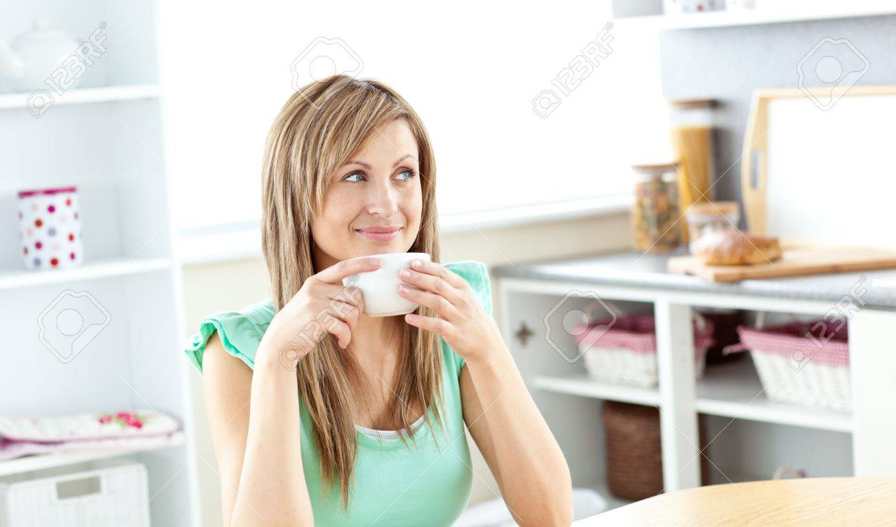 Blond caucasian woman drinking coffee in the kitchen Stock Photo - 10246438
