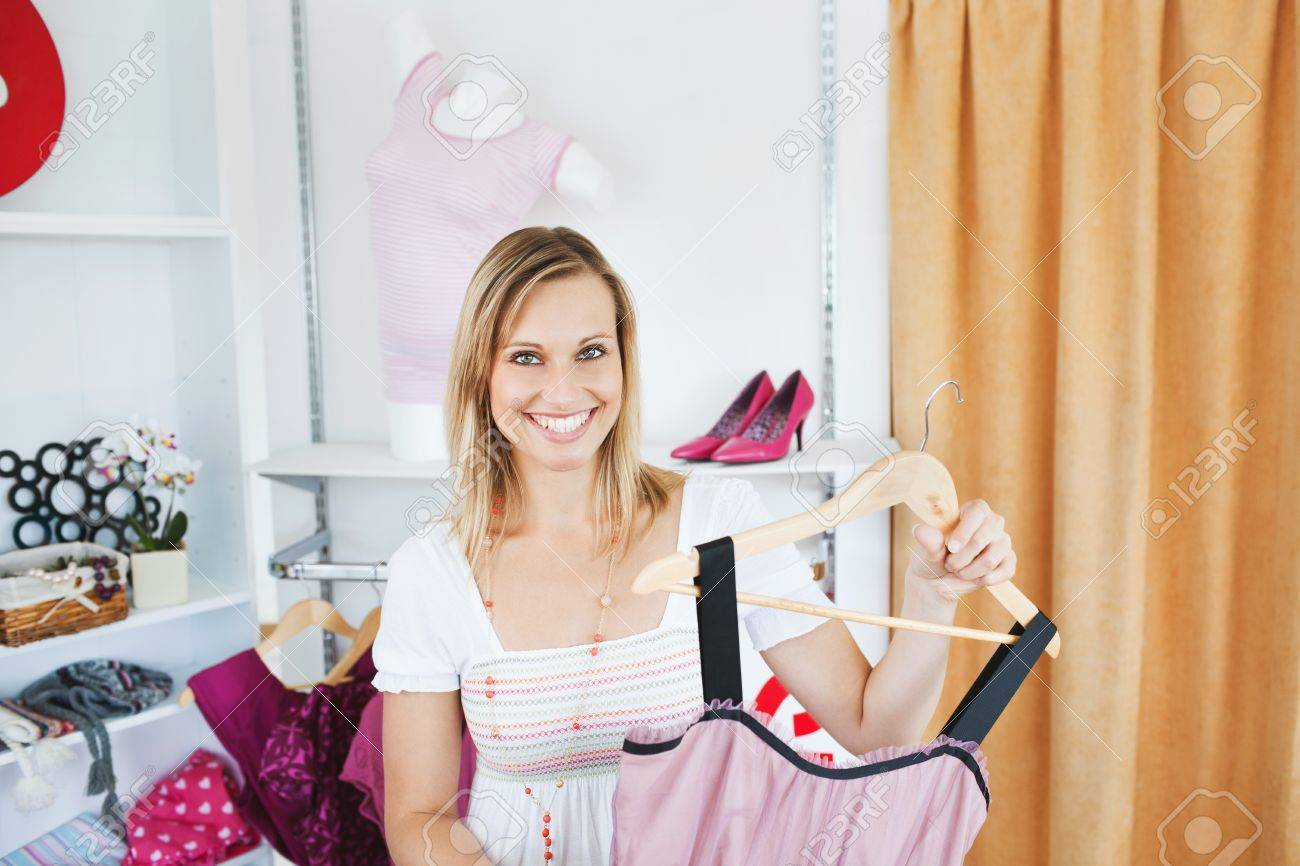 Positive  woman holding a dress smiling at the camera Stock Photo - 10248915