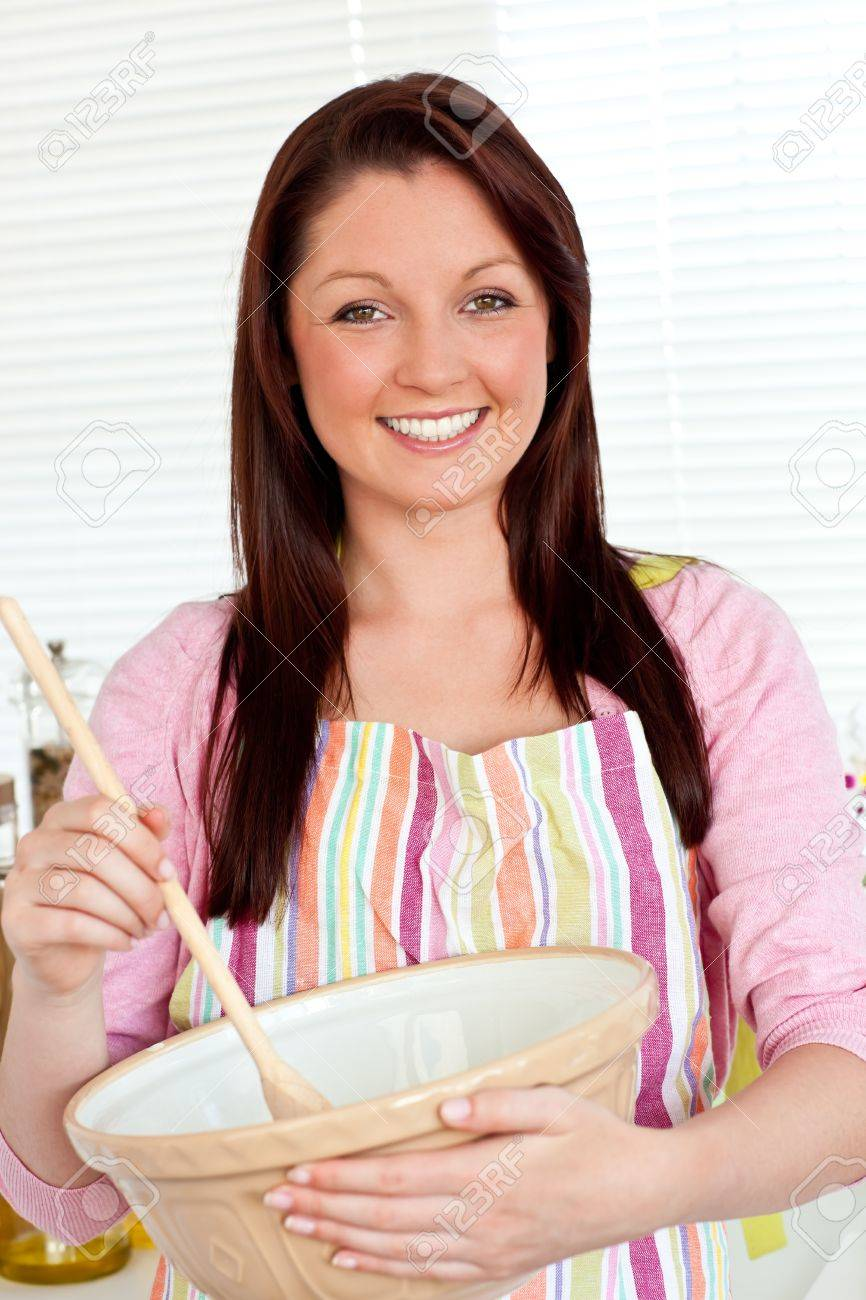 Smiling woman cooking a cake at home Stock Photo - 10248772