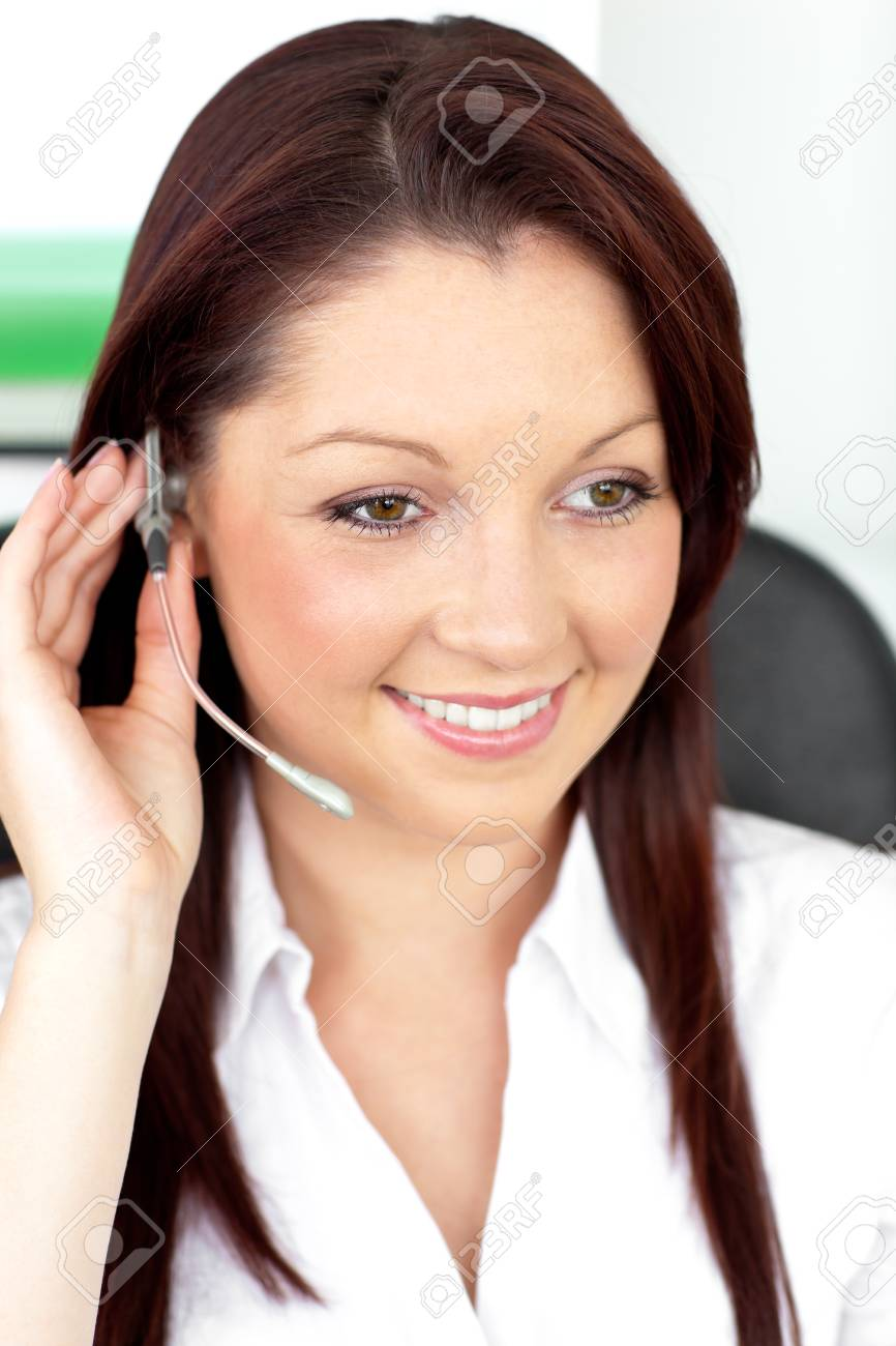 Positive young businesswoman sitting at her desk and wearing earpiece Stock Photo - 10242568