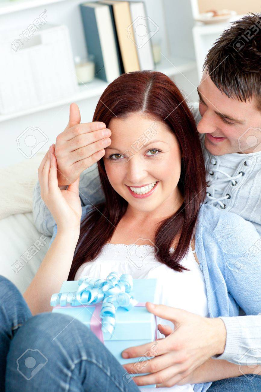 Surprised girlfriend being offered a present by her boyfriend in the living-room Stock Photo - 10243144