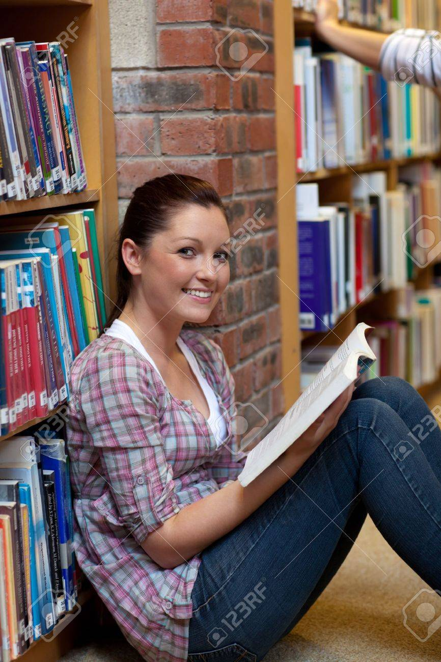 Smiling young woman reading a book sitting on the floor Stock Photo - 10243408