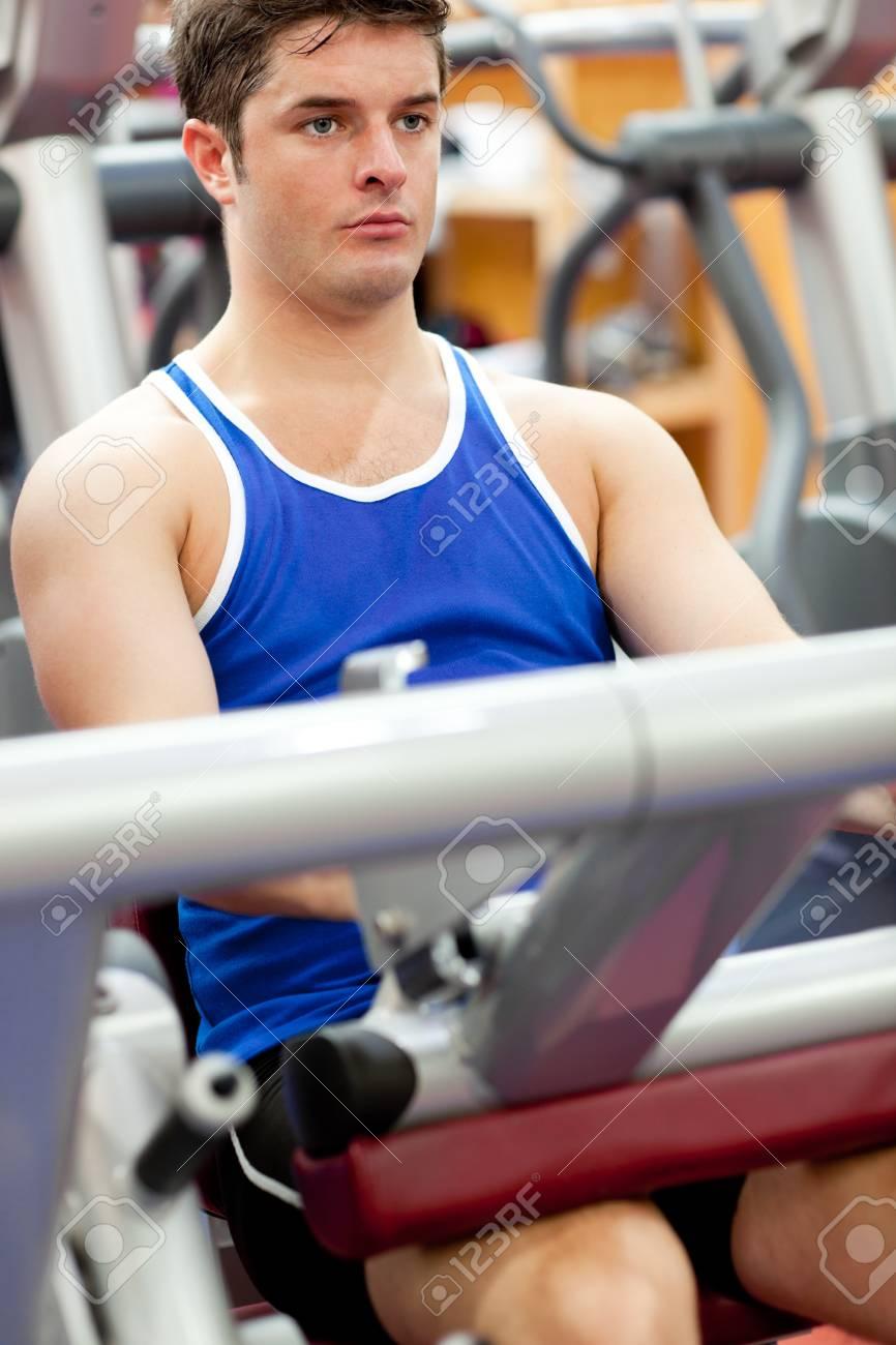 Serious young man using a leg press Stock Photo - 10244271