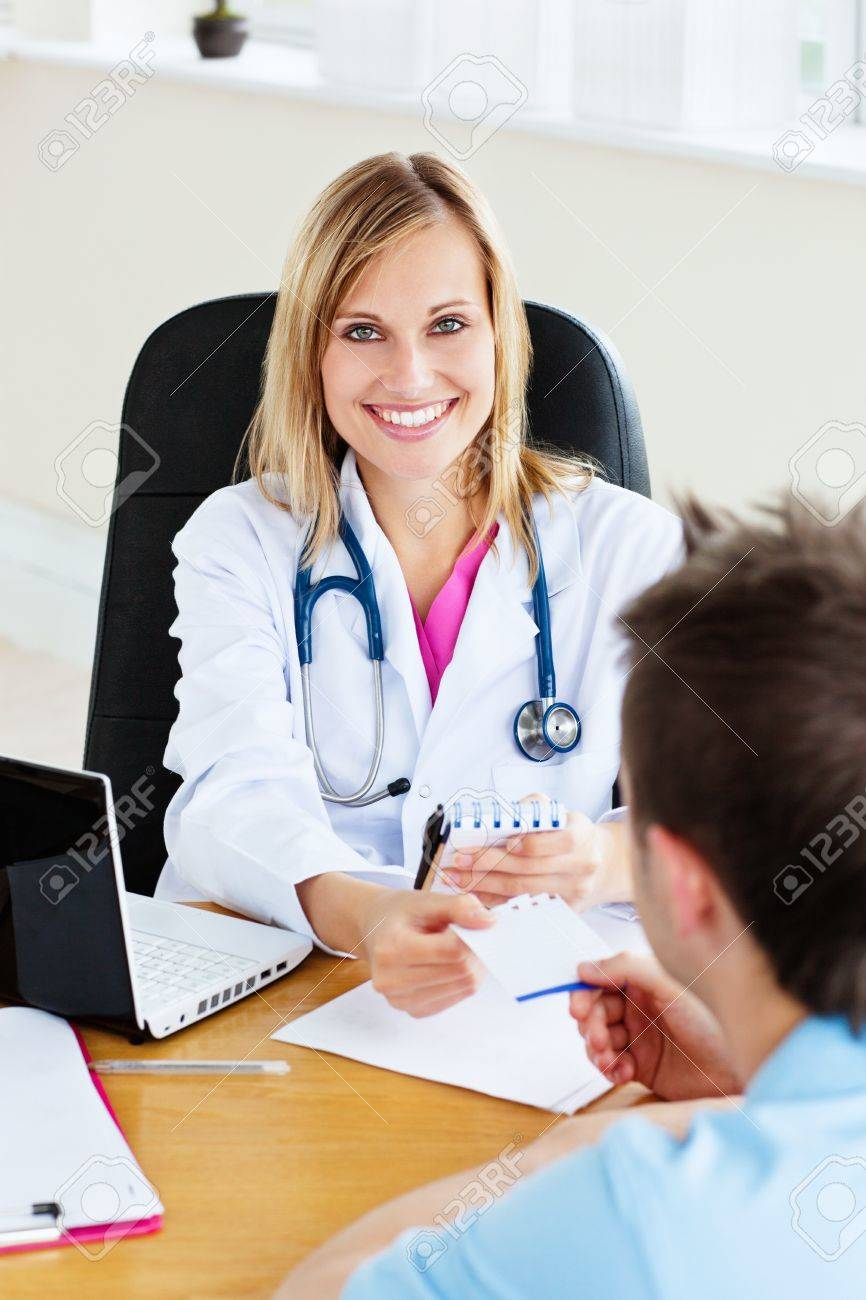 Joyful female doctor giving a prescription to her patient in the office Stock Photo - 10244455