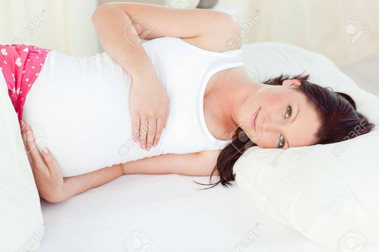 Young pregnant woman resting in her bed in the bedroom Stock Photo - 10243785