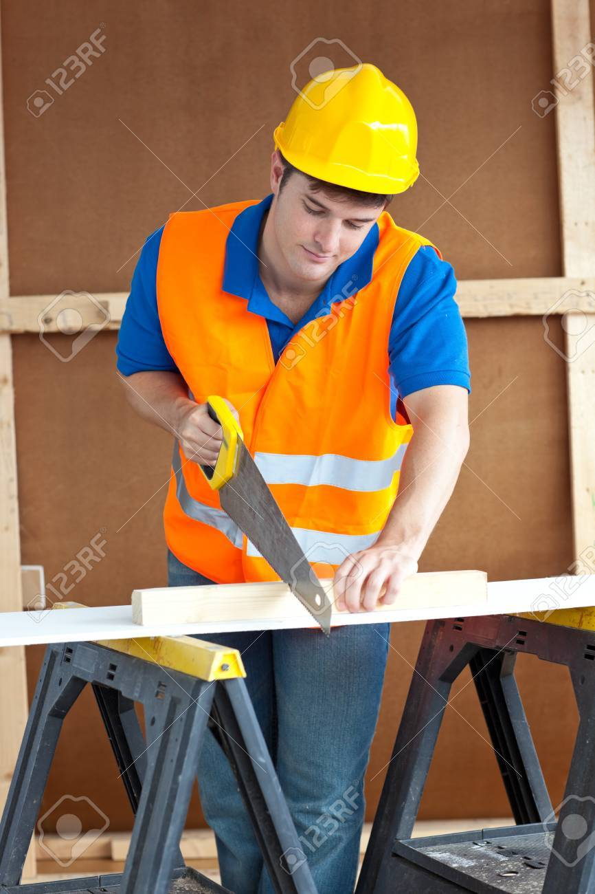 Handsome male worker wearing a yellow hardhat sawing a wooden board Stock Photo - 10244274