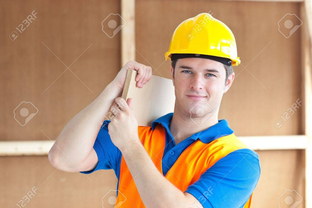 Confident young male worker with a yellow helmet carrying a wooden board Stock Photo - 10244136