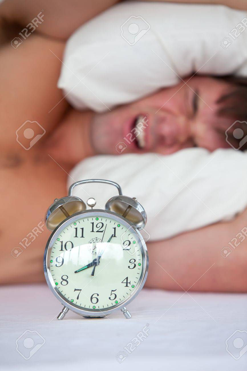 Angry Young Man Lying In Bed And Annoyed By His Alarm Clock In ...
