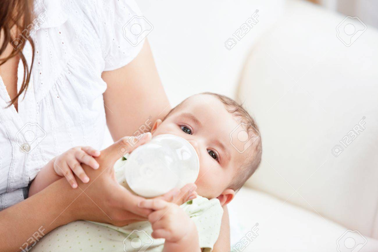 Caring mother feeding her adorable son in the kitchen Stock Photo - 10243681
