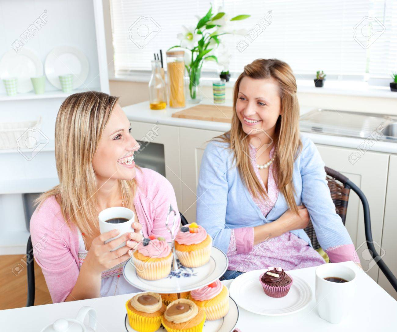 Female friends with cakes and coffee speaking together in the kitchen Stock Photo - 10245038