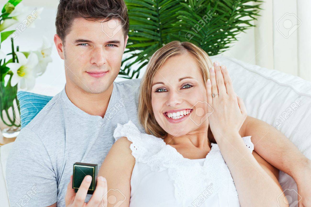Blissful woman showing her wedding ring to the camera lying with her boyfriend Stock Photo - 10254491