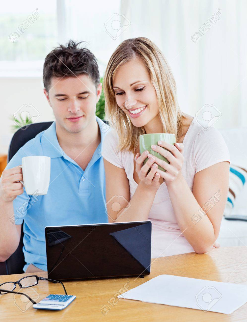 Happy couple using a laptop sitting together at a table holding cups of coffee Stock Photo - 10254102