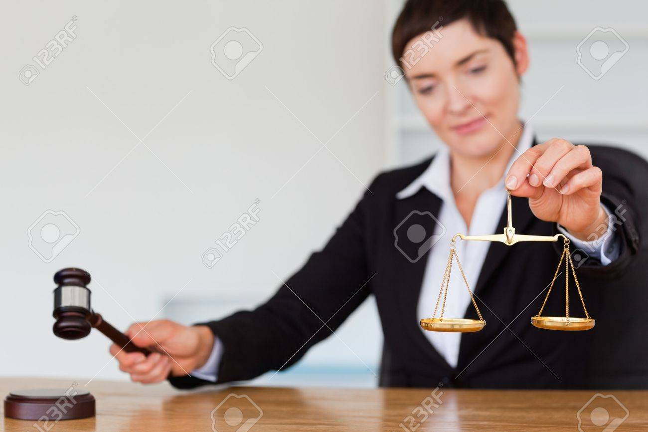 Serious judge with a gavel and the justice scale in her office Stock Photo - 10784506