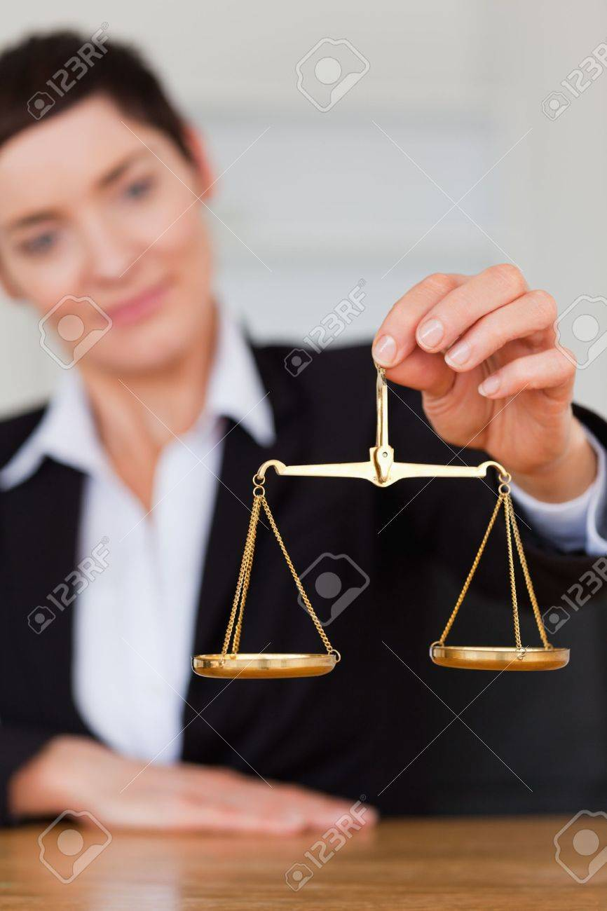 Serious woman holding the justice scale in her office Stock Photo - 10786761