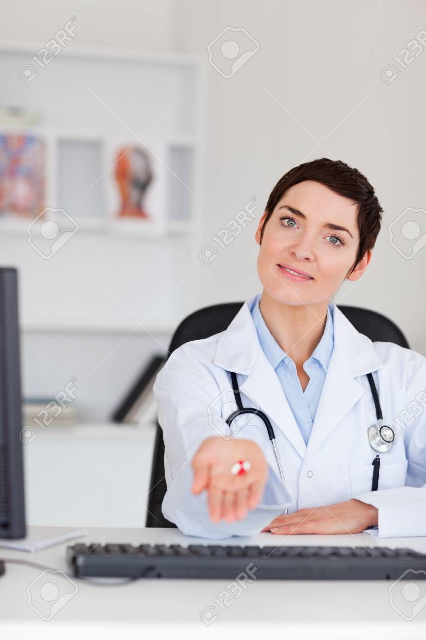 Portrait of a doctor showing pills in her office Stock Photo - 10780354