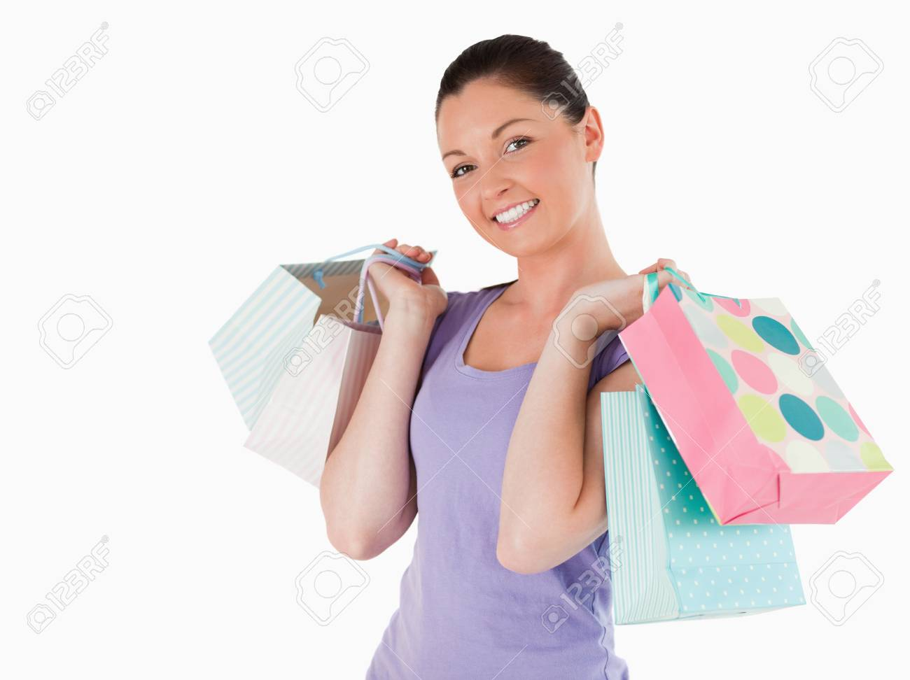 Gorgeous woman holding shopping bags while standing against a white background Stock Photo - 11180057