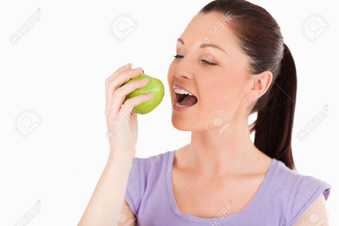 Lovely woman eating an apple while standing against a white background Stock Photo - 11191378