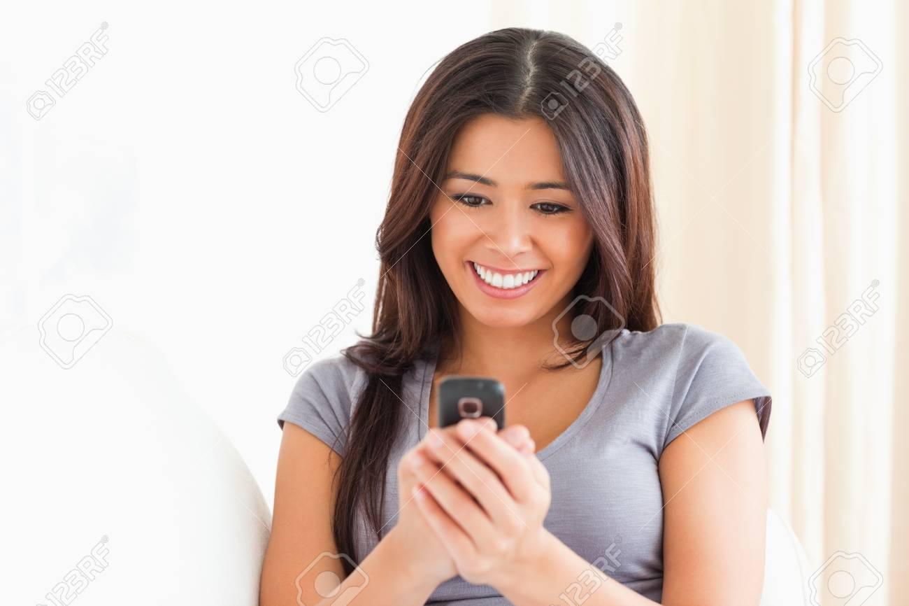 close up of a cheerful woman looking at mobile phone in livingroom Stock Photo - 11191813
