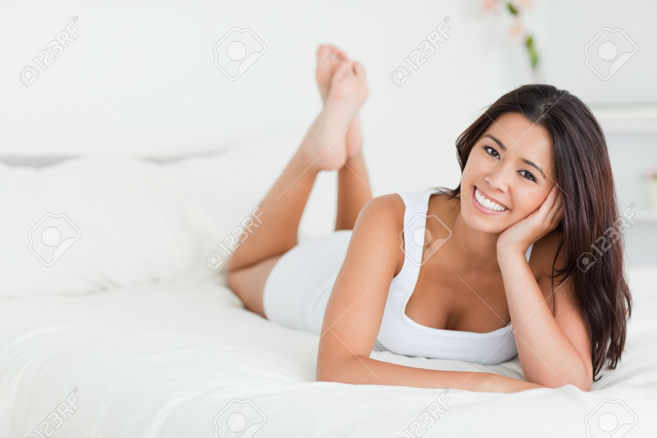 happy woman lying on bed with crossed legs looking into camera in bedroom Stock Photo - 11201922