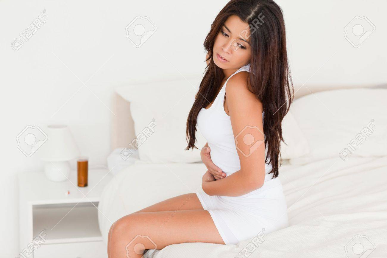 goodlooking woman having stomach ache looking into camera in bedroom Stock Photo - 11202334