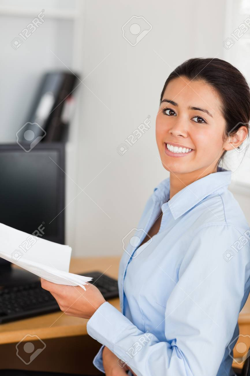 Beautiful woman holding a sheet of paper and posing while sitting at the office Stock Photo - 11204629