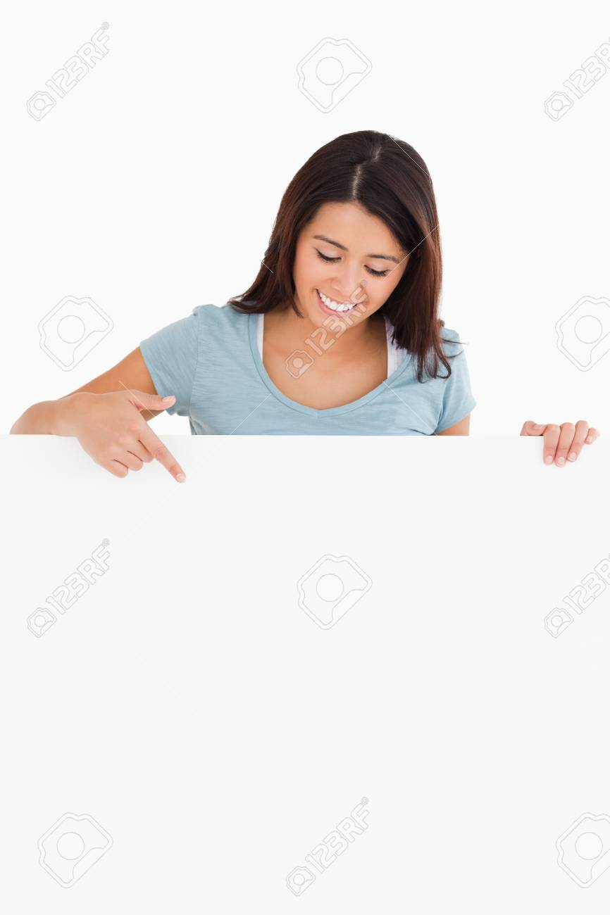 Gorgeous woman pointing at a board while standing against a white background Stock Photo - 11197781