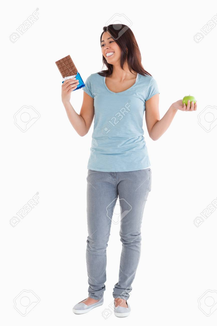 Gorgeous female holding a chocolate bar and an apple while standing against a white background Stock Photo - 11198051