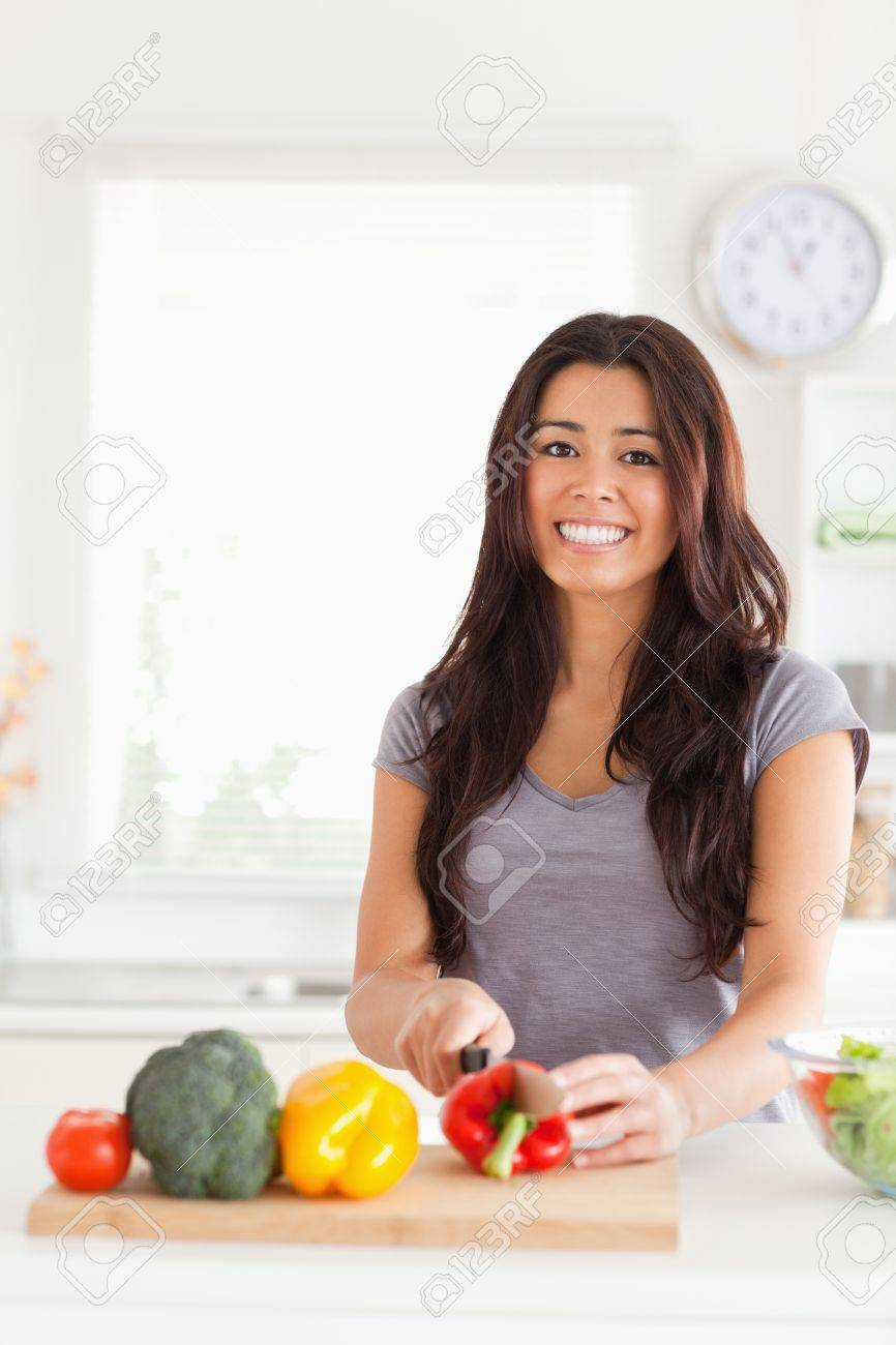 Pretty woman cooking vegetables while standing in the kitchen Stock Photo - 11204552