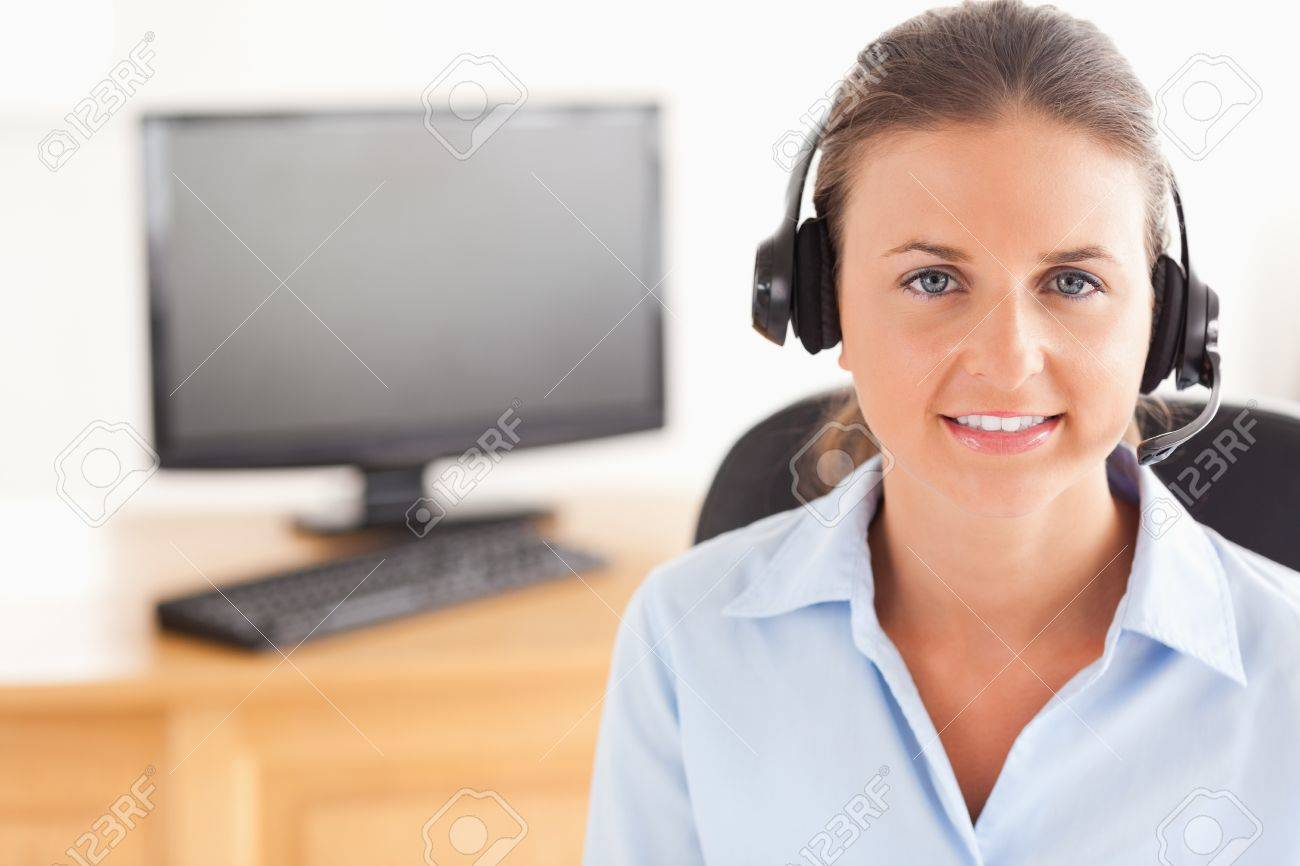 Office worker wearing a headset posing  in her office Stock Photo - 11203434