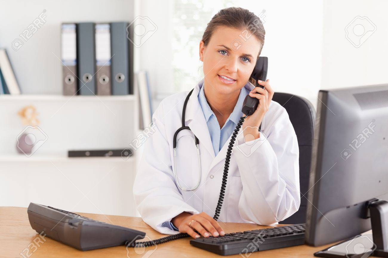 Serious female doctor on the phone in her office Stock Photo - 11204824