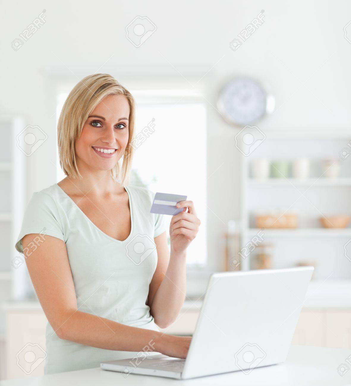 Blonde woman with credit card and notebook looks into camera in the kitchen Stock Photo - 11198050