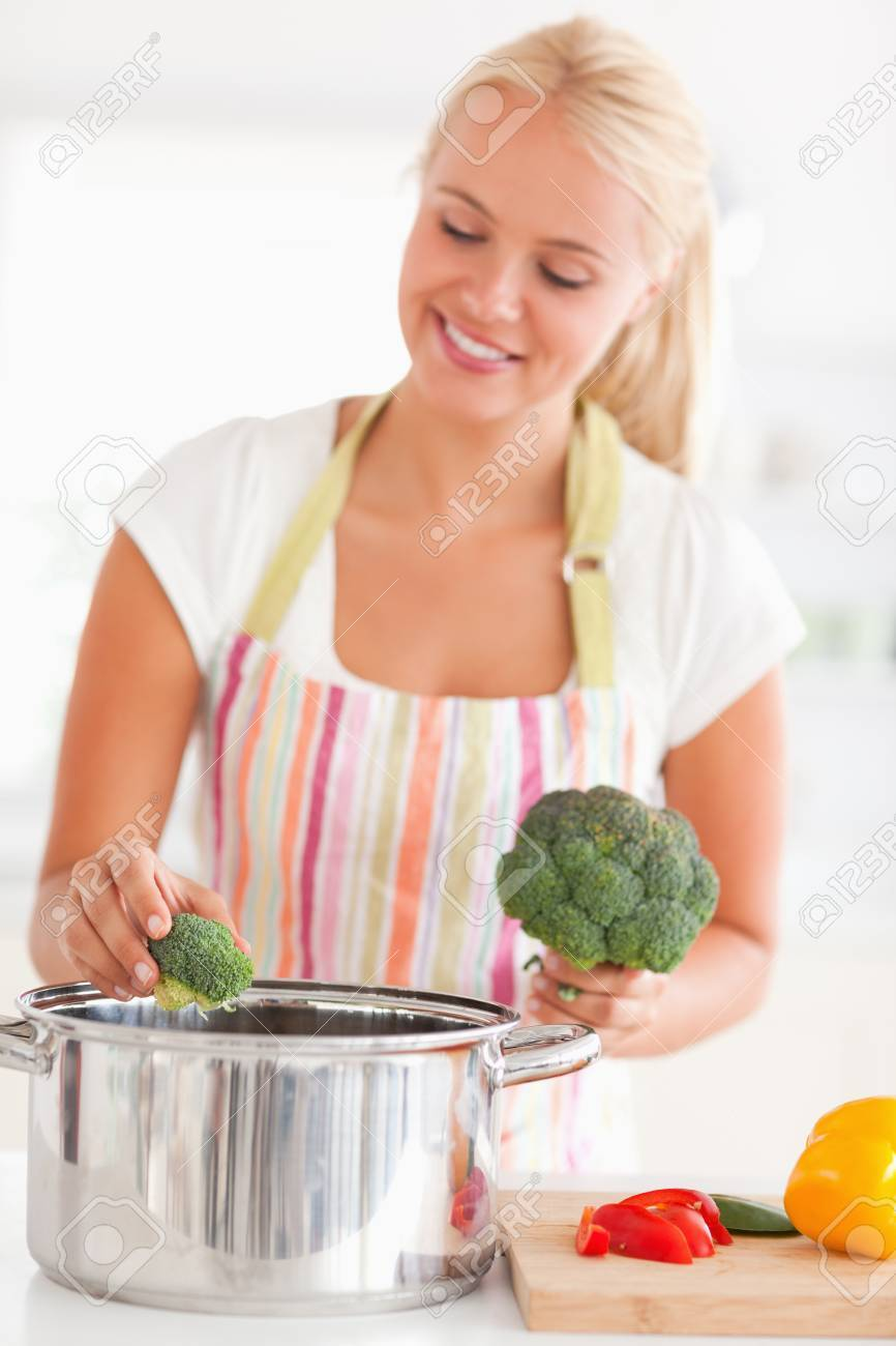 Portrait of a woman putting cabbage on water in a kitchen Stock Photo - 11231278