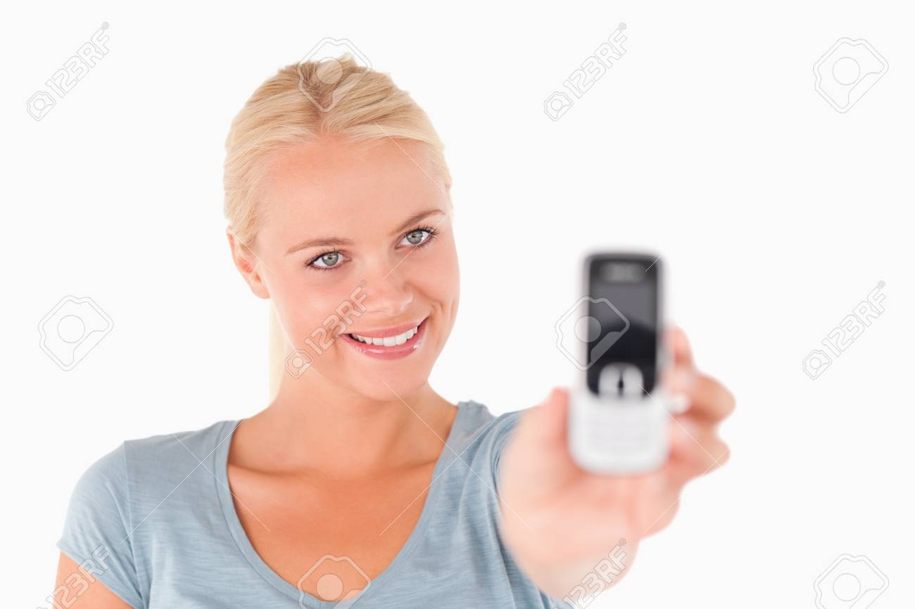 Smiling woman showing a mobile in a studio Stock Photo - 11206478