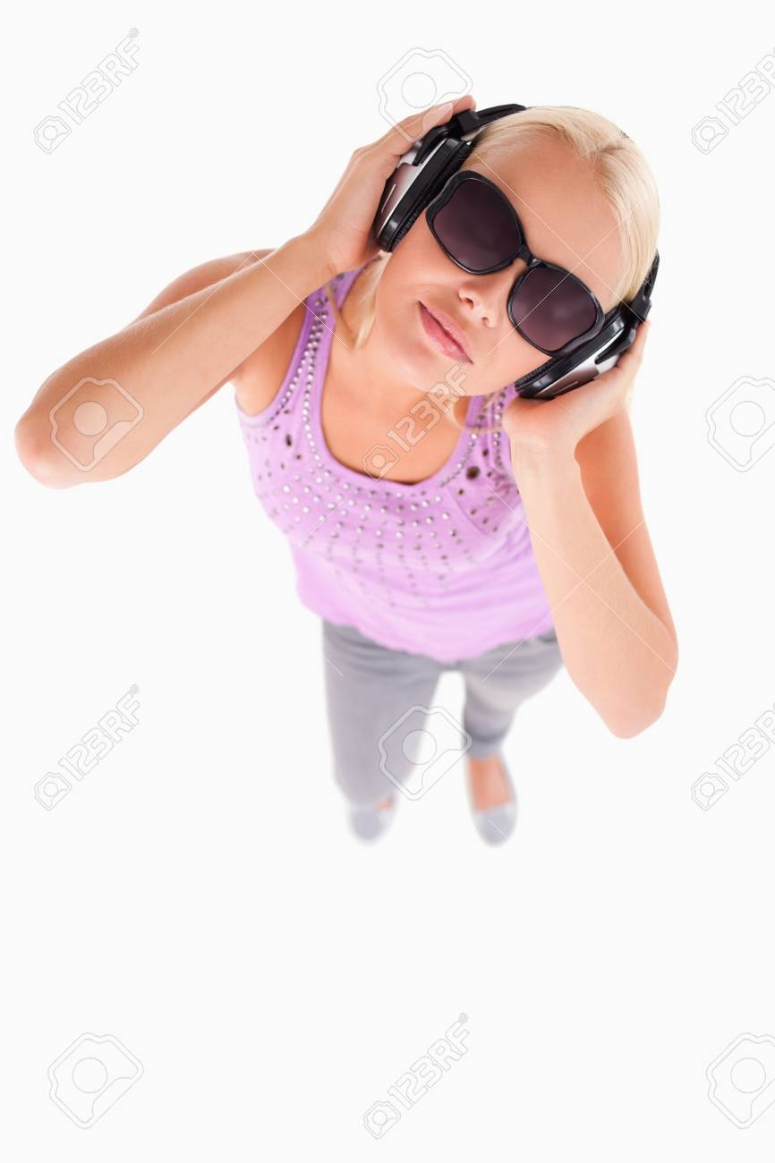 Gorgeous lady with sunglasses and earphones in a studio Stock Photo - 11206409