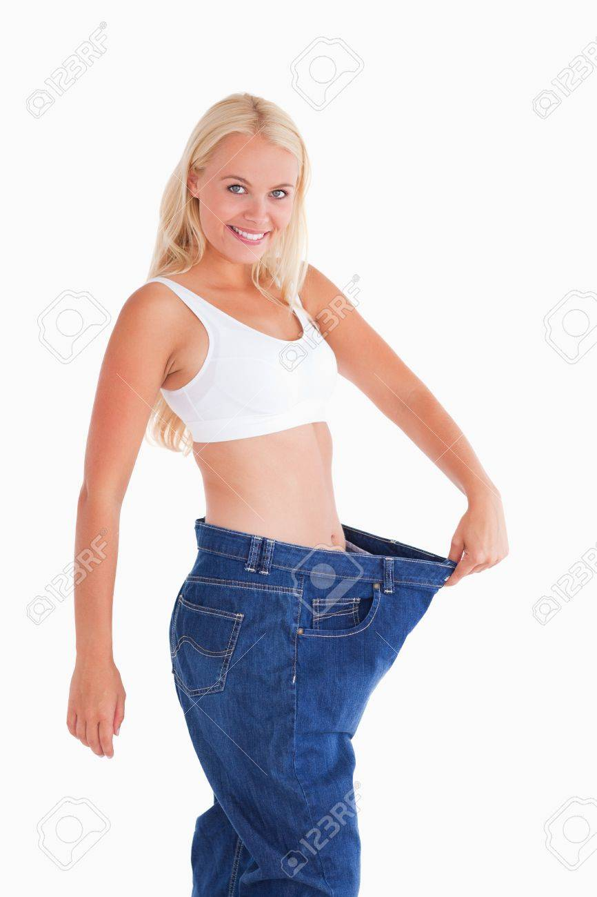 Cute woman wearing to big jeans in a studio Stock Photo - 11207694