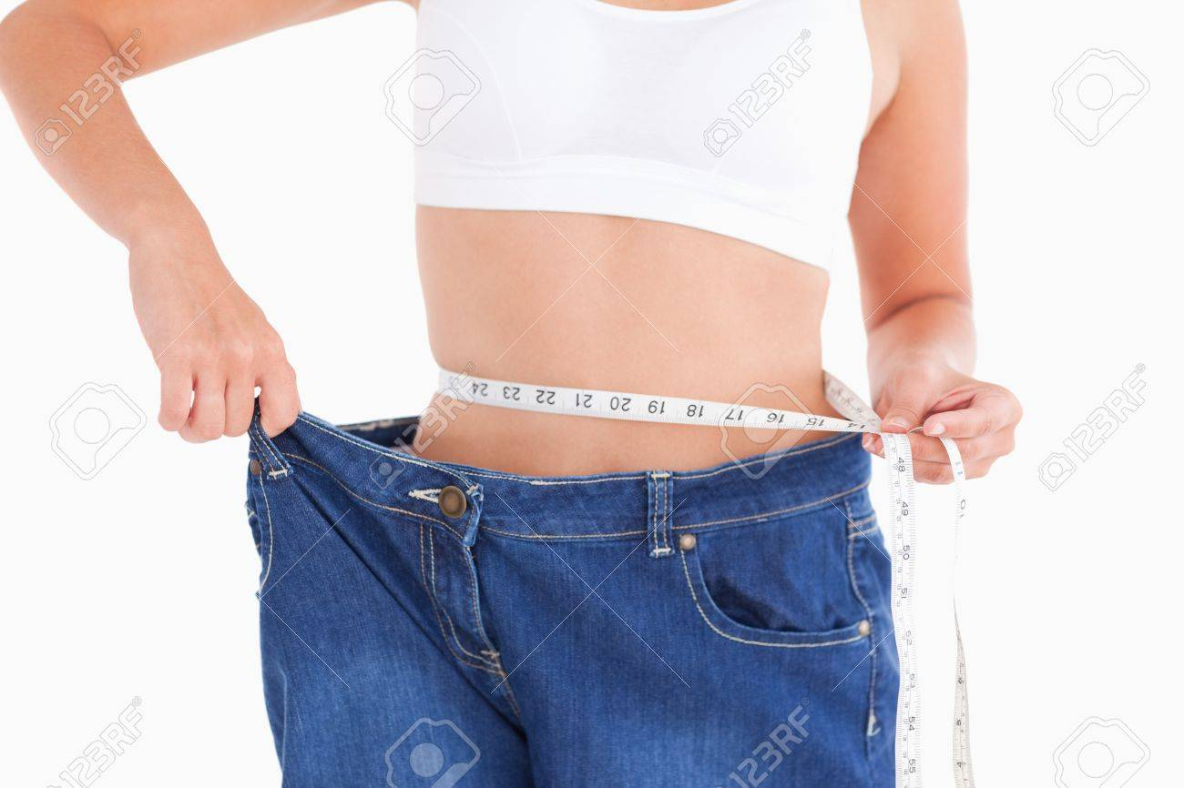 Woman measuring her waist while wearin too big jeans in a studio Stock Photo - 11232966