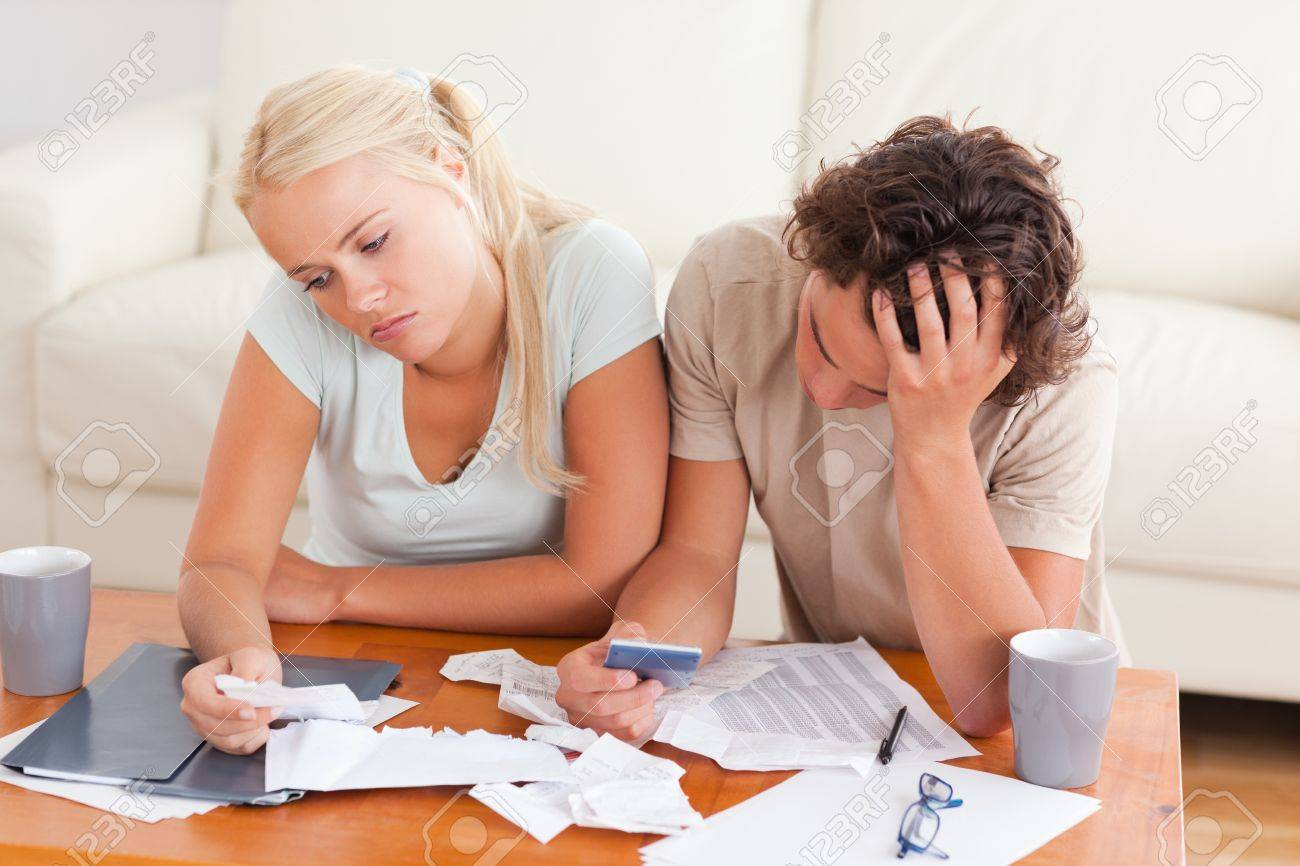 Unhappy couple listing expenses in the living room - 11227128