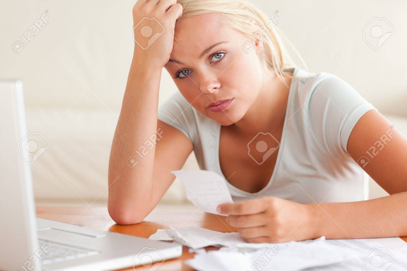Worried woman accounting looking into the camera in the living room Stock Photo - 11228887