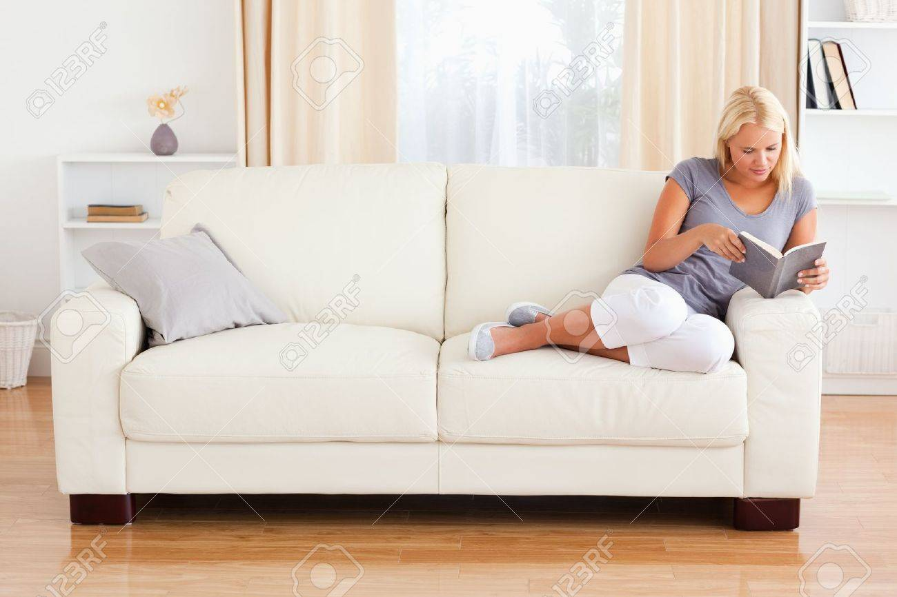 Woman reading a book in her living room Stock Photo - 11192365