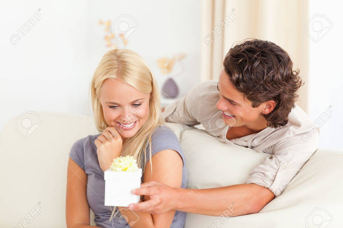 Man offering a present to his fiance in their living room Stock Photo - 11192326