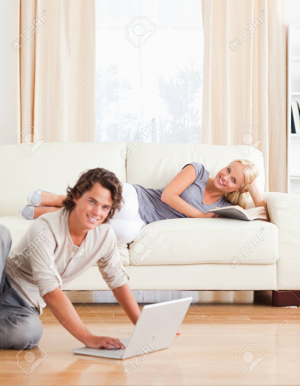 Portrait of a man with a laptop while his girlfriend is with a book looking at the camera Stock Photo - 11225206