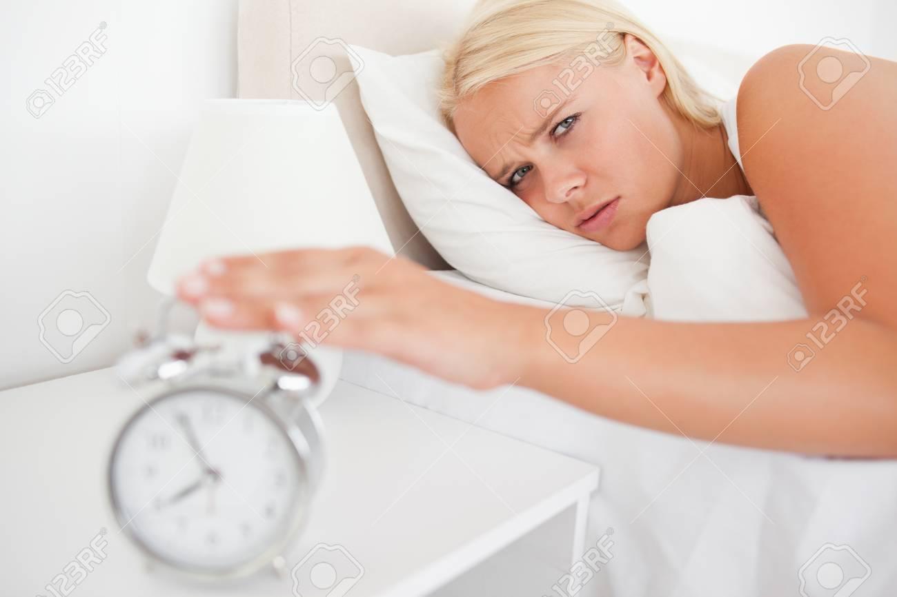 Tired woman awaken by an alarmclock in her bedroom Stock Photo - 11230518