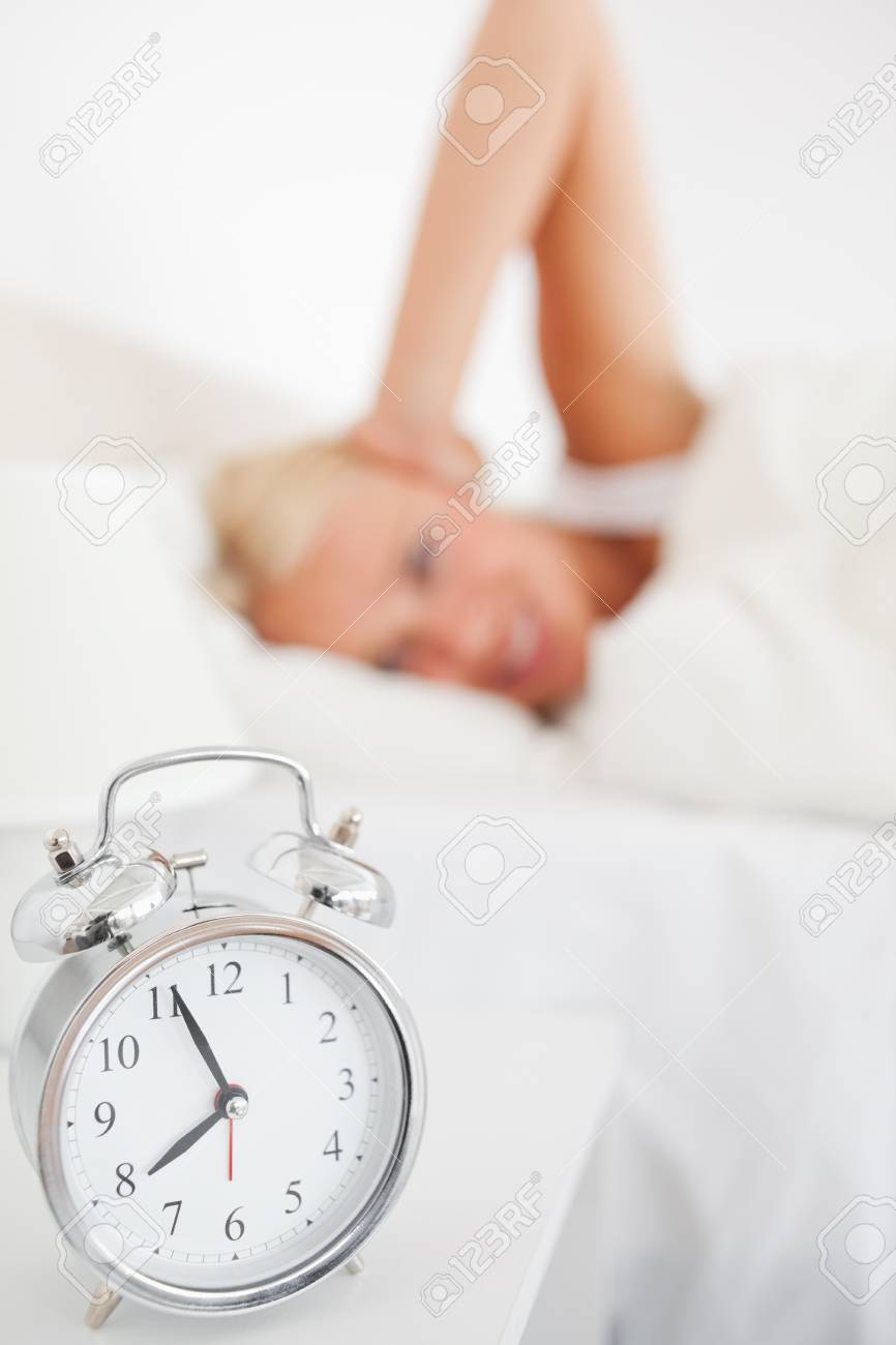 Alarmclock waking up a woman with the camera focus on the object Stock Photo - 11225923