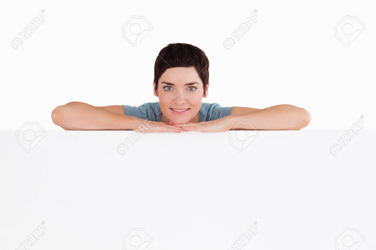 Serene woman relying on a blank panel against a white background Stock Photo - 11227902