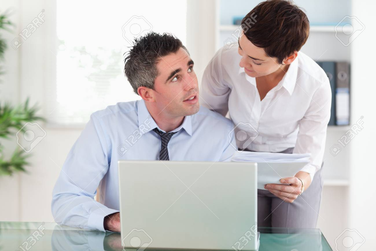 Smiling colleagues comparing a blueprint folder to an electronic one in an office Stock Photo - 11189960