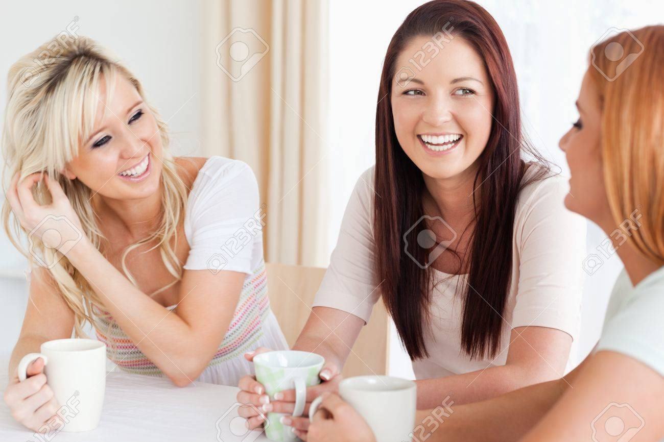 Joyful young Women sitting at a table with cups in a kitchen Stock Photo - 11188912
