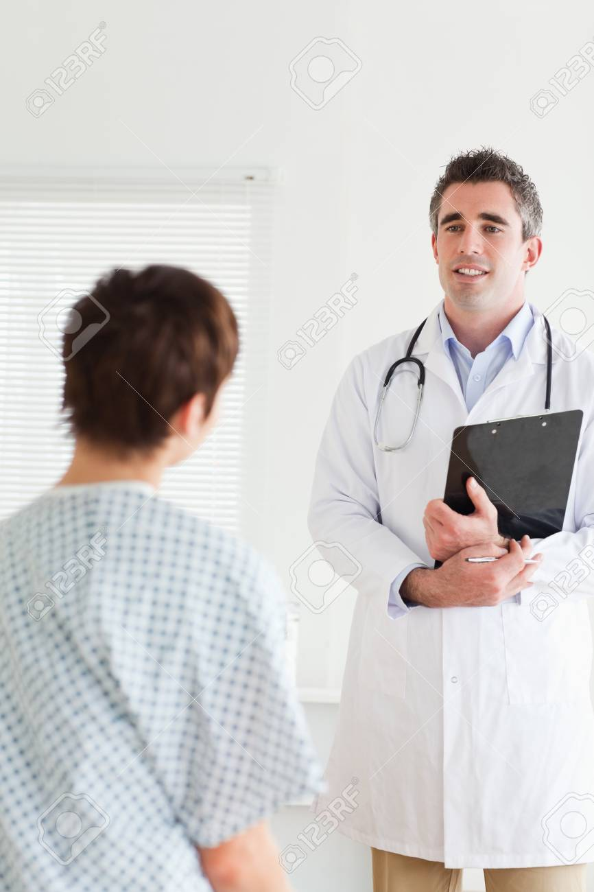 Doctor Talking To A Cute Woman In Hospital Gown In A Room Stock ...