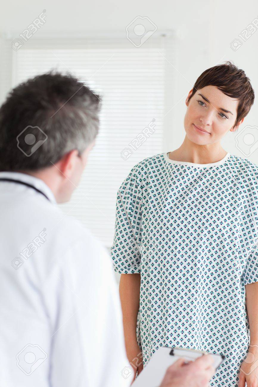 Cute Woman In Hospital Gown Talking To Her Doctor In A Room Stock ...
